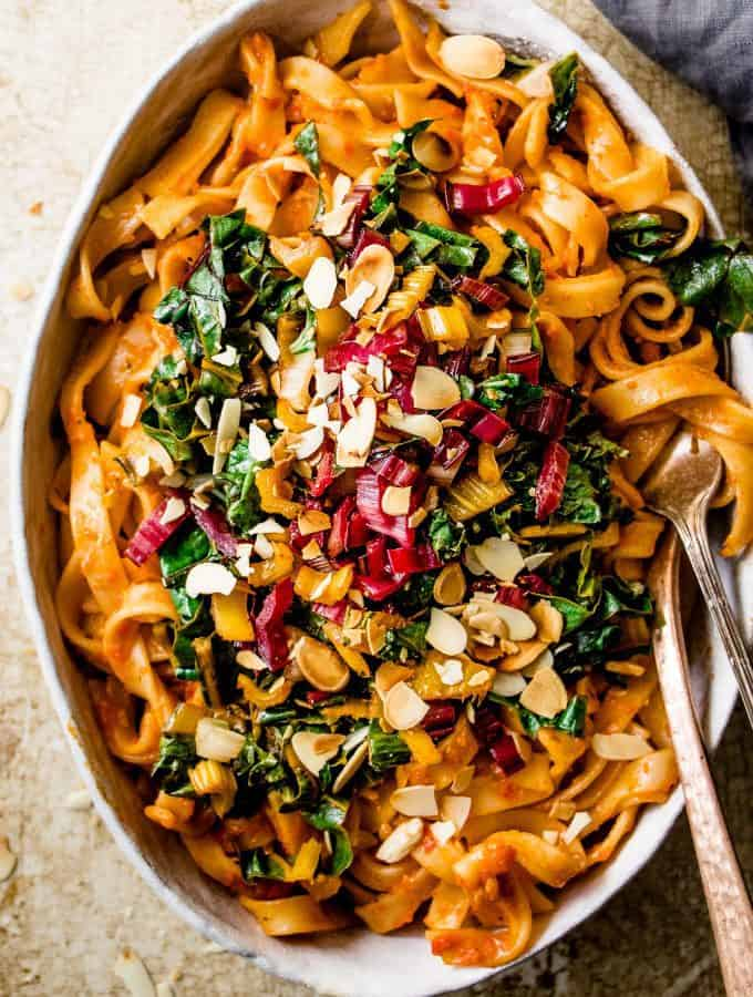 Roasted red pepper pasta with wilted greens in a white dish with a fork and spoon.
