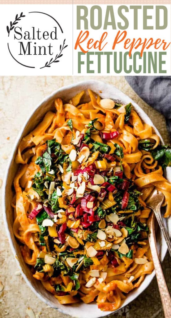 Creamy red pepper pasta with greens and text overlay.