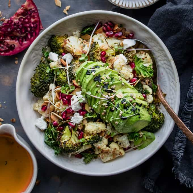 This healthy glow broccoli and lemon winter salad is the perfect mid winter nourish bowl. Roasted broccoli and cauliflower drizzled with a lemon garlic dressing and topped with all the winter essentials. Pomegranate, toasted almonds and goat's cheese. #veggie #plantbased #salad #wintersalad