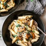 Bowl of creamy mushroom pasta with fork and napkin.