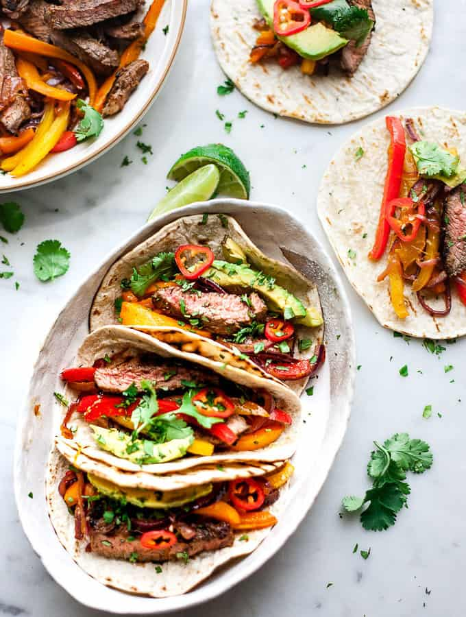 beef fajitas in a bowl with peppers and avocado