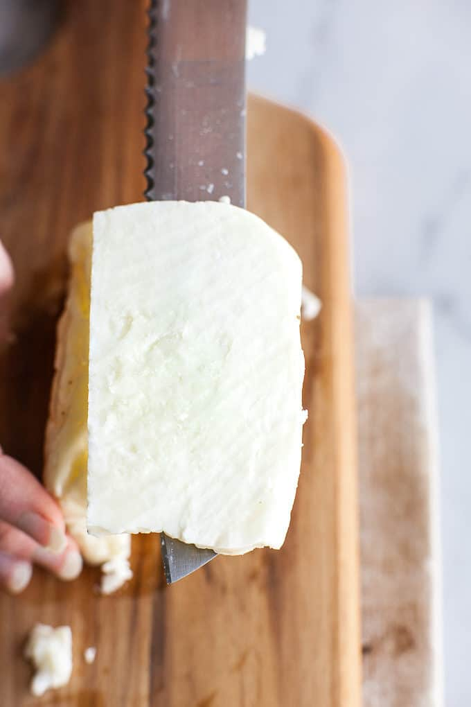 Slice of halloumi resting on a knife.
