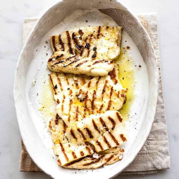 Grilled halloumi in a bowl with olive oil and salt.