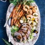 Roast leg of lamb platter with side dishes and spoons.