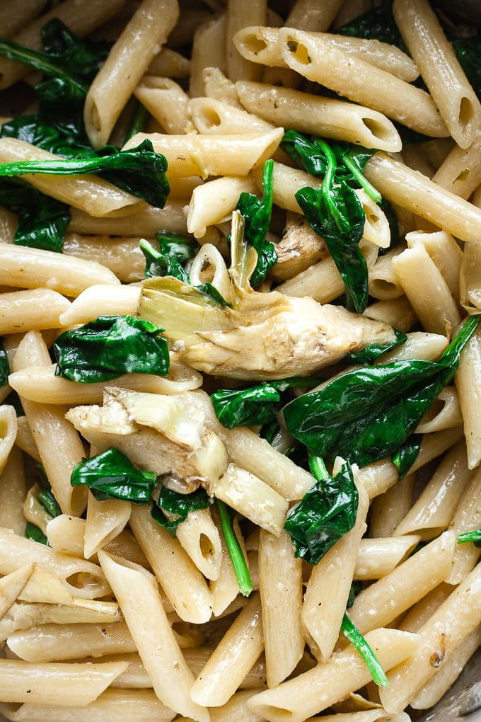 Close up of pasta with artichokes and spinach in a pan.