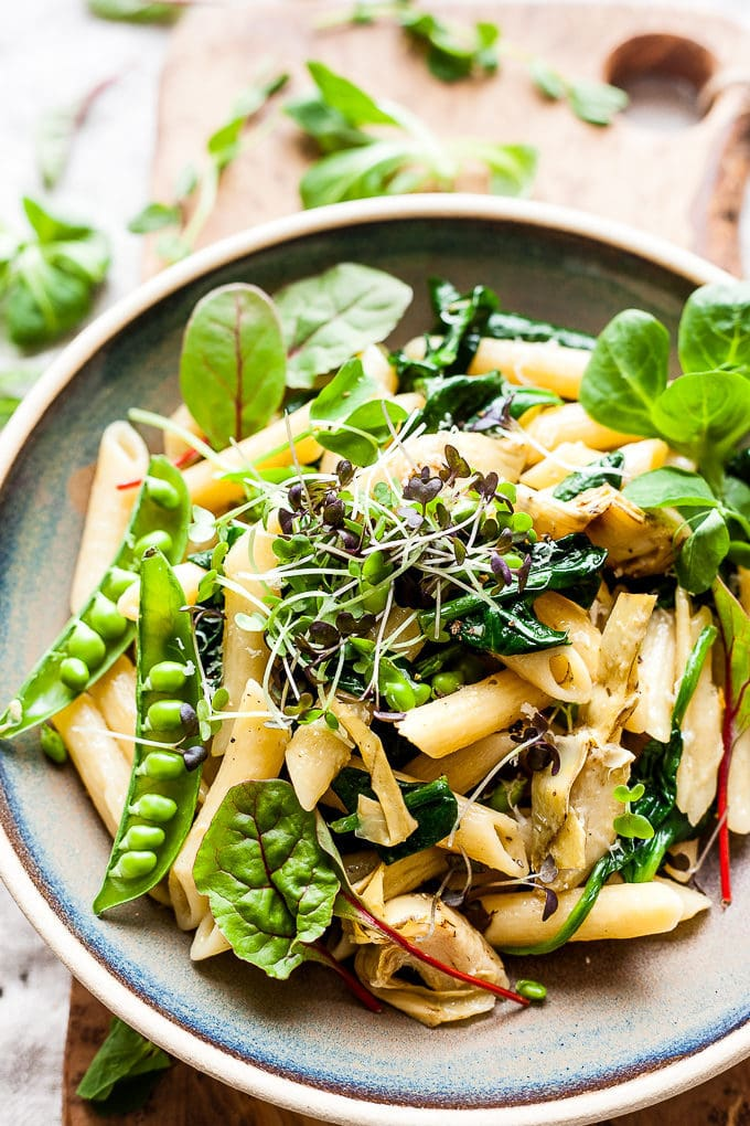 Artichoke pasta with greens in a bowl.