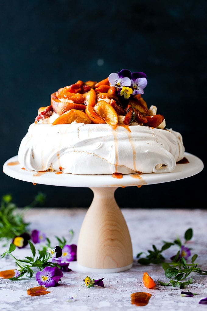 roasted peach pavlova with flowers on a cake stand.
