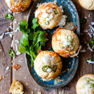 Cheddar jalapeno cornbread muffins with a blue plate.
