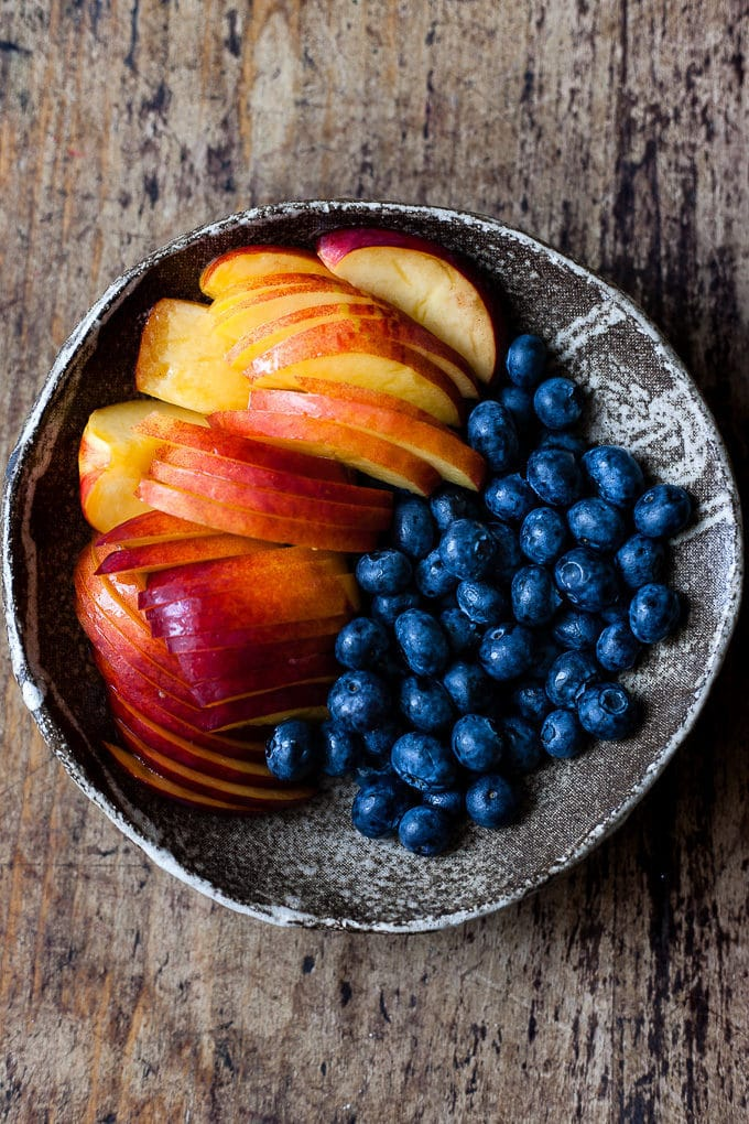 Blueberries and sliced nectarines in a bowl for blueberry coffee cake.