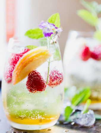 Peach sangria in a glass with raspberries