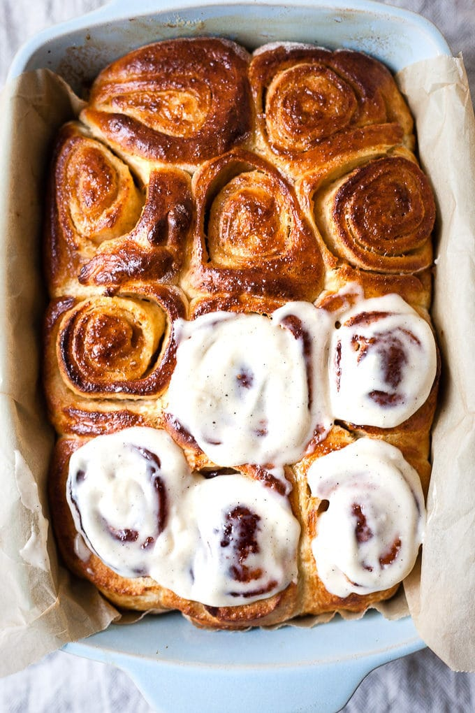Cinnamon roll from scratch being frosted.