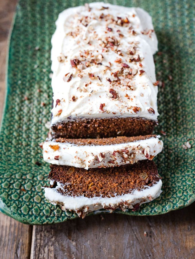 Whole carrot cake loaf on a green serving plate.
