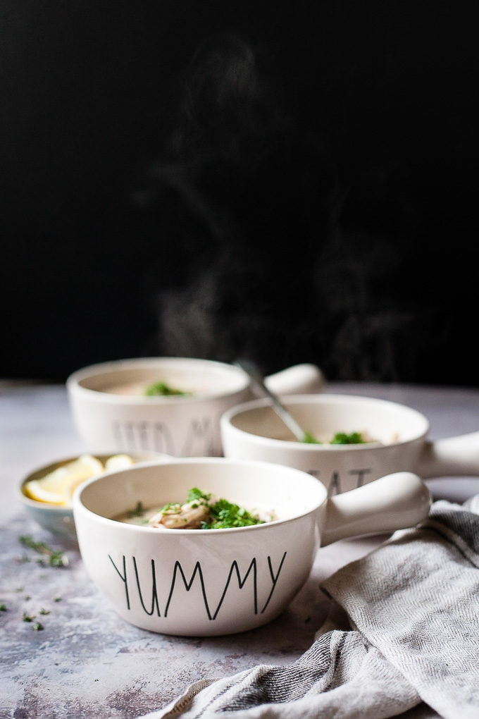 3 bowls Creamy chicken wild rice soup against a black background with steam coming off them.
