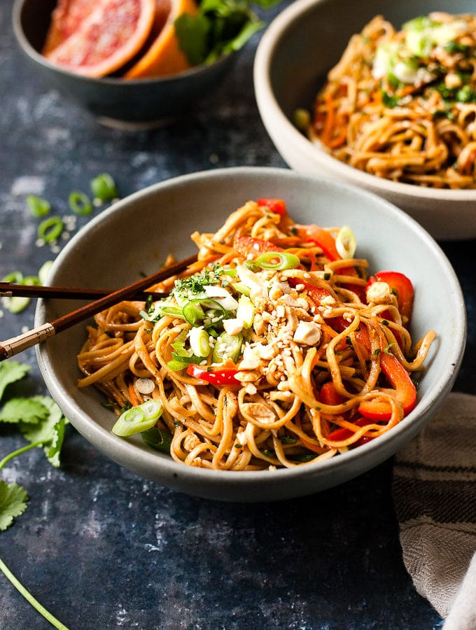 thai peanut noodles in a blue bowl with blood oranges and chop sticks.