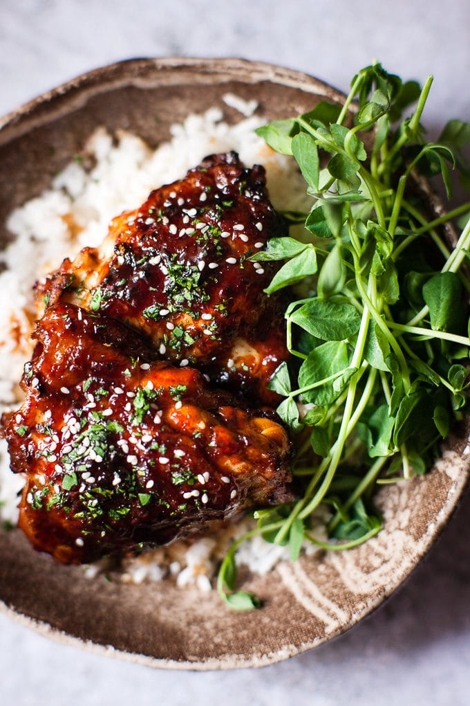 Baked Honey chicken in a bowl with sesame seeds, rice and greens.