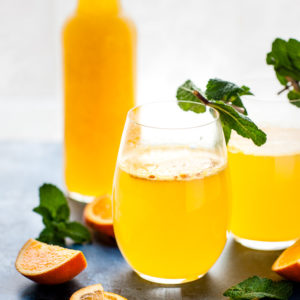 Orange Ginger Immune boosting elixir in a bottle with a glass on the side.