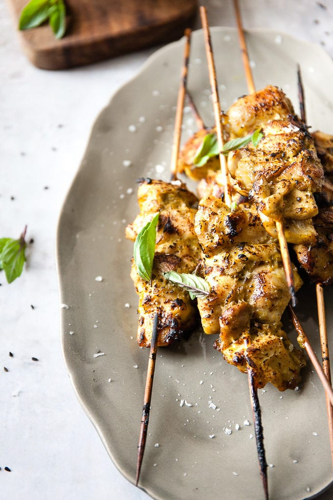 Close up of chicken skewers on a plate with basil leaves.