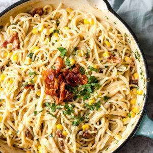 Skillet of creamy one pot pasta with corn and bacon. Overhead view.