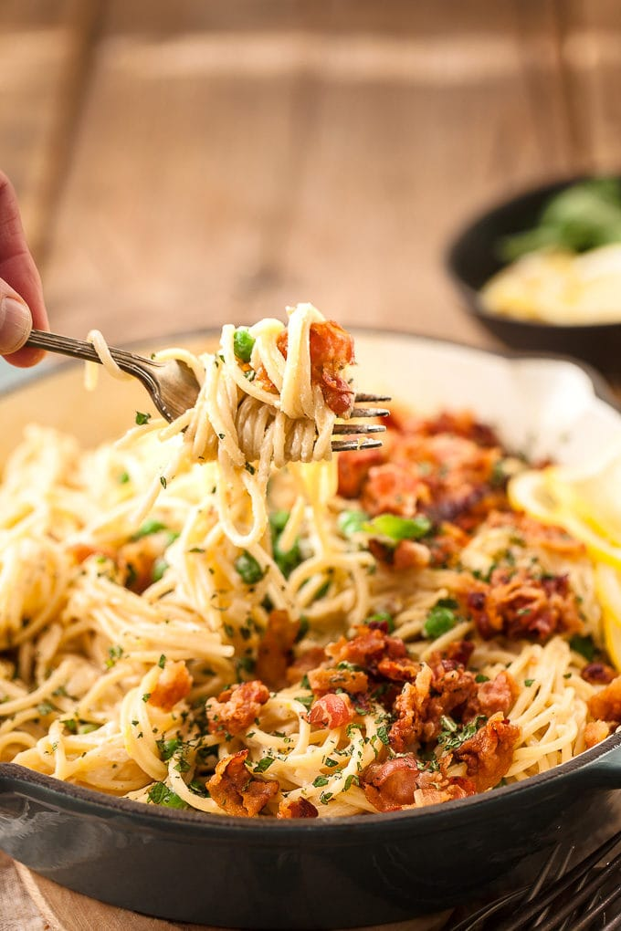 Close up of the bacon and pea pasta on a fork being held in a hand.